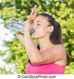 Fitness Woman Refreshing by water after running outdoor.