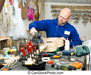 craftsman working with unfinished guitar - Concentrated...