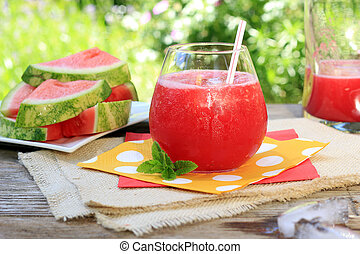 Watermelon drinks outside in the garden with straws and...