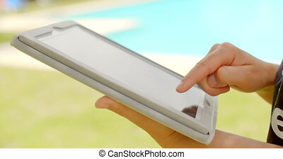 Woman Working on Tablet Device in Swimming Pool Area at Slow...