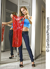 young woman fits on a dress - beautiful woman fits on a red...