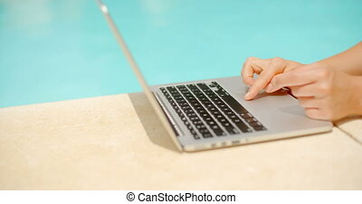 Woman Working on Her Laptop in Swimming Pool Area in Slow...
