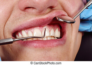 man patient having her teeth examined by specialist