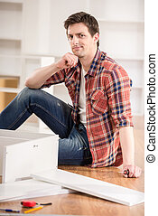 Furniture installation - Young man dressed casual assembling...