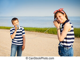 Kids having a phone call with tin cans on sea background