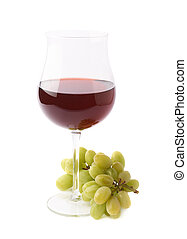 Glass of red wine next to a branch of grapes