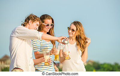 Group of happy young people drinking beer on the beach -...