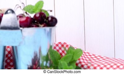Cherries in small metal bucket on the wooden table.