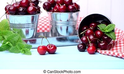 Cherries in small metal bucket on the wooden table