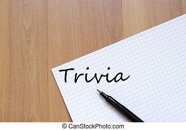 Trivia concept - White blank notepad on office wooden table...