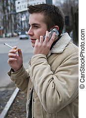 Young smoker on the phone - Young smoking man with a mobile...