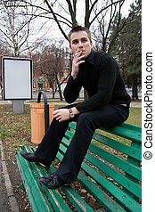 Young smoker outdoors - Young adult man smoking on the bench...