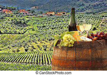 White wine with barrel on vineyard in Chianti, Tuscany,...