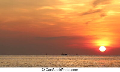 panorama of boat drifting at background of sun disk rising...