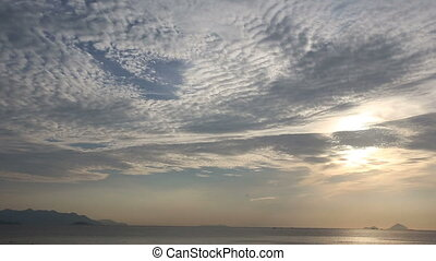 fantastic motion of white clouds above sea at dawn -...
