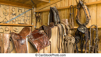 Horse Gear - Horse saddles and other horse gear hanging on a...