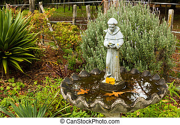 Monk Bird Bath - Old bird bath with monk statue in the...