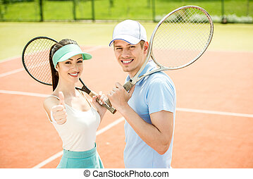 Tennis - Smiling young couple standing on tennis court,...