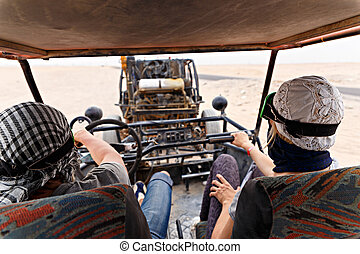 Young couple riding buggy car in desert