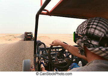 Men riding buggy car in desert and having fun