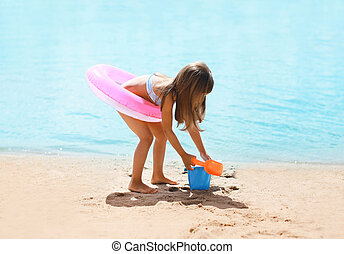 Child with inflatable rubber circle having fun on the beach...