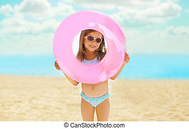 Portrait of happy child with inflatable rubber circle having...