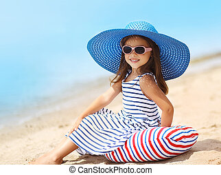 Portrait of pretty little girl in a striped dress and straw hat relaxing on the beach near sea, summer, vacation, travel - concept