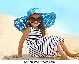 Portrait of pretty little girl in a striped dress and straw hat sitting on the beach near sea, summer, vacation, travel - concept