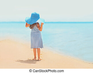 Summer travel photo pretty little girl in dress and straw hat enjoying on the beach near sea, vintage colors