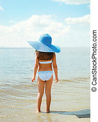 Summer travel photo pretty little girl in straw hat on the beach near sea