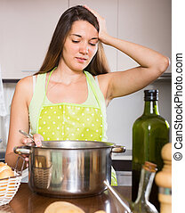 Girl thinking what to cook - Young girl cooking first dish...