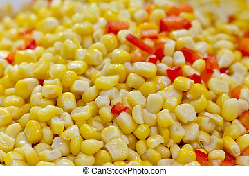 Closeup of tinned whole kernel corn and carrots, it could be...