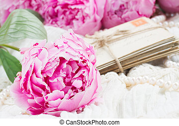 pink a peony on lace - fresh pink peonies with pile of old...