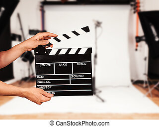 Man with film clapper in studio - Man hands holding film...