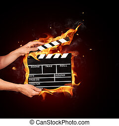 Man with film clapper in fire - Man hands holding film...