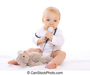 Portrait of baby playing with stethoscope and teddy bear