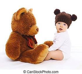 Portrait of cute baby in knitted brown hat with big teddy bear