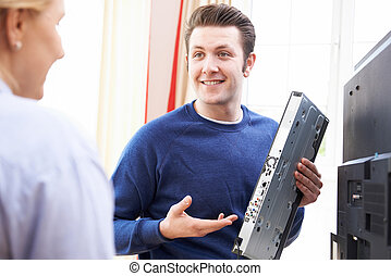 Engineer Giving Advice On Installing Digital TV Equipment
