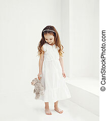 Sweet little girl with teddy bear in white room