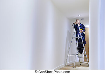 Female Electrician Installing Lights In Ceiling