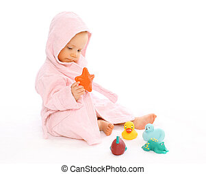 Baby in bathrobe playing with water rubber toys
