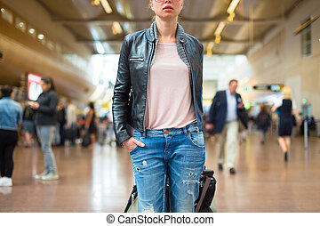 Female traveller walking airport terminal. - Casually...