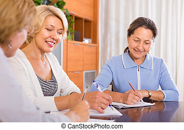 Senior ladies signing documents - Happy smiling senior...