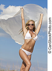 A beautiful young blond woman wearing a white bikini and sunglasses with white material blowing in the wind, shot against a blue sky