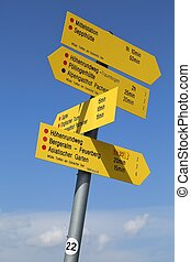 Direction signs against clear blue sky