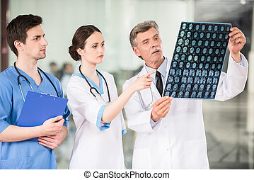 Medicine - Group of doctors looking at X-ray at offie