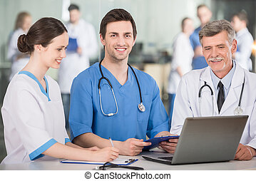 Medicine - Group of doctors working together on a laptop at...