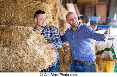 Two farm workers in hayloft - Portrait happy farm workers...