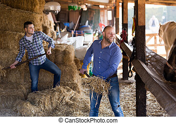 Two farm workers feeding horses - Two russian farm workers...