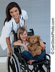 Little girl on a wheelchair holding her teddy bear